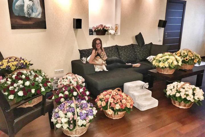 Ольга в гостиной в окружении цветов