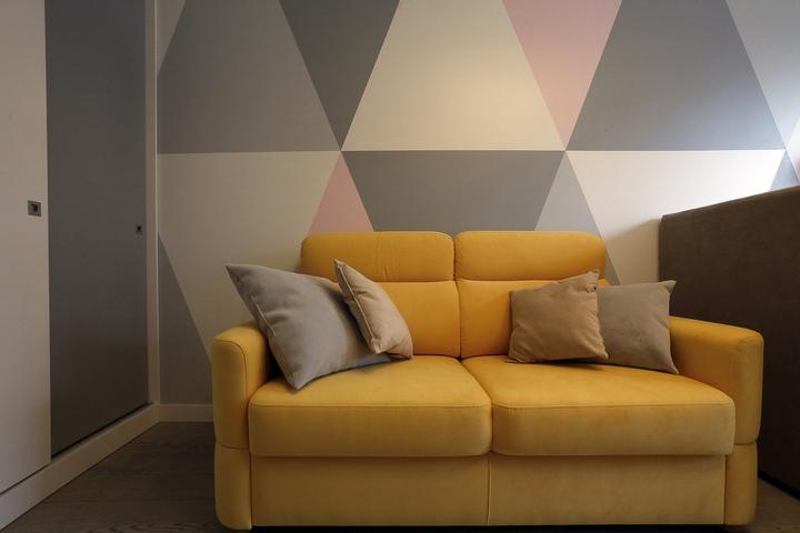 Акцентный желтый диван на фоне сложного рисунка