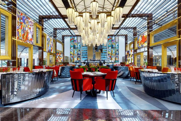 Вид на главный зал ресторана: большая люстра, столики и диваны с зеркалами