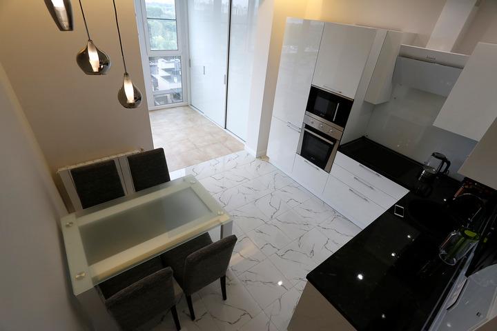 Технологичная кухня со стеклянной мебелью и глянцевыми поверхностями