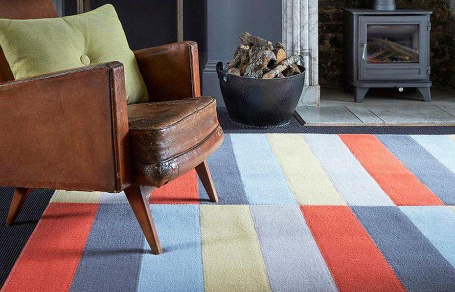 Многоцветный полосатый ковер как функциональный элемент декора