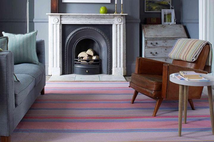 Цветовой акцент на полосатом ковре зрительно вытягивает комнату по направлению полос