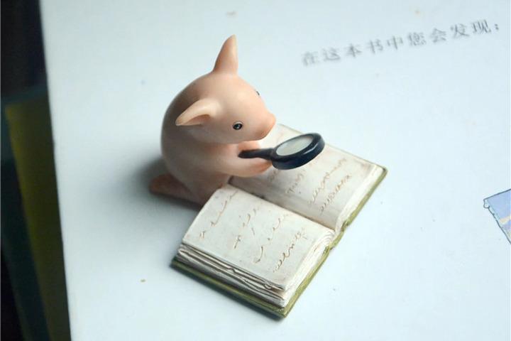 Фигурка свинки, которая читает книгу