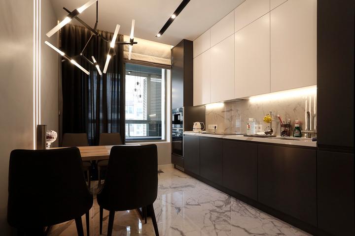 Подсветка над рабочей зоной кухни и люстра над столом