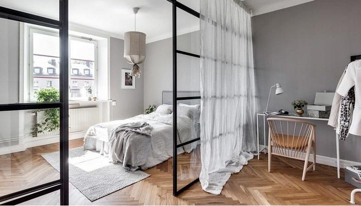 Выделенная стеклянной перегородкой и шторой спальня