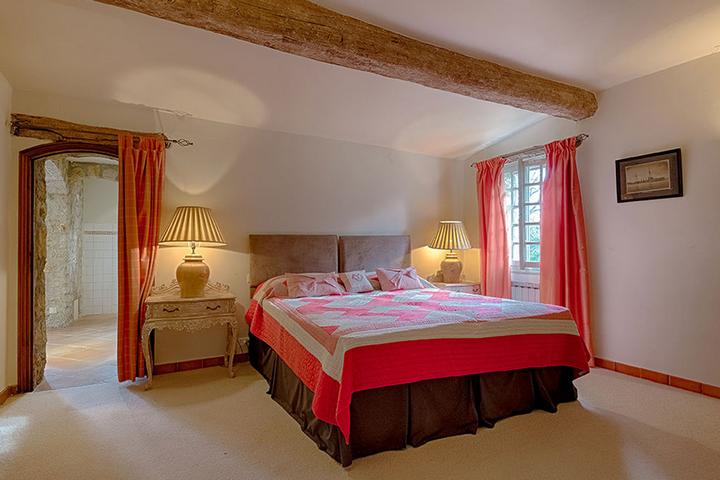Одна из спален с ярким текстилем и деревянными элементами