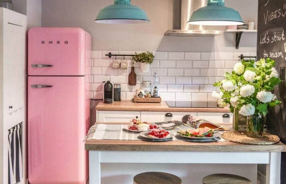 Яркий розовый холодильник в небольшой кухне