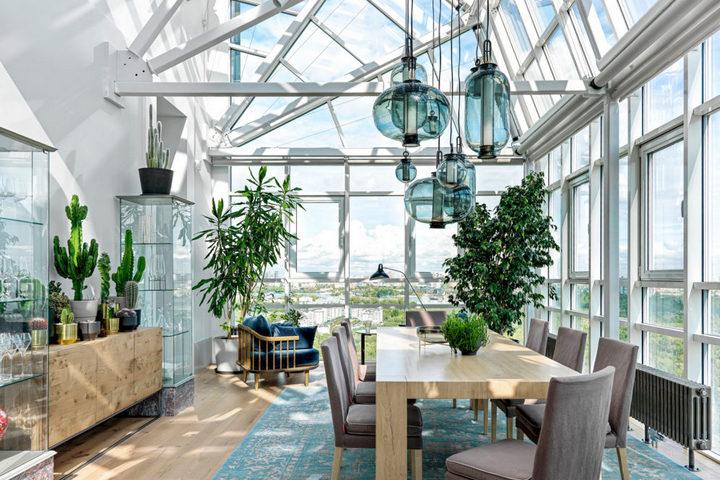 Зимний сад с высокими потолками, множеством стекла и деревянной мебелью